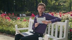 Νεαρός άνδρας στο πάρκο που χρησιμοποιεί ένα lap-top και μια ταμπλέτα Στοκ φωτογραφία με δικαίωμα ελεύθερης χρήσης