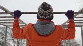 Νεαρός άνδρας στο πορτοκαλί σακάκι που κάνει pullups στους οριζόντιους φραγμούς υπαίθρια το χειμώνα απόθεμα βίντεο