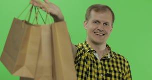 Νεαρός άνδρας στο πράσινο βασικό υπόβαθρο χρώματος οθόνης με τις τσάντες αγορών απόθεμα βίντεο
