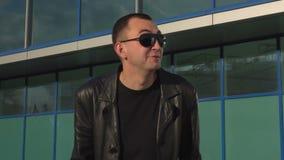 Νεαρός άνδρας στο σακάκι δέρματος και γυαλιά ηλίου έκπληκτα ή συγκεχυμένα, υπαίθριος απόθεμα βίντεο
