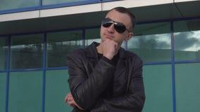 Νεαρός άνδρας στο σακάκι δέρματος και στάση γυαλιών ηλίου υπαίθρια και σκέψη φιλμ μικρού μήκους