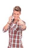 Νεαρός άνδρας στο τηλέφωνο που δείχνει σε σας Στοκ Φωτογραφίες