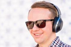 Νεαρός άνδρας τα ακουστικά σύγχρονης, καλής ποιότητας που συνδέονται με με δικούς του Στοκ φωτογραφίες με δικαίωμα ελεύθερης χρήσης