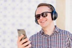 Νεαρός άνδρας τα ακουστικά σύγχρονης, καλής ποιότητας που συνδέονται με με δικούς του Στοκ Φωτογραφία
