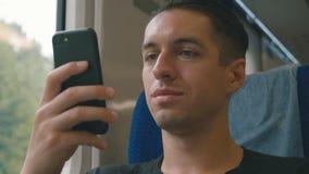 Νεαρός άνδρας χρησιμοποιώντας το smartphone του, δένοντας με ταινία και τυλίγοντας κατά τη διάρκεια του γύρου τραίνων φιλμ μικρού μήκους
