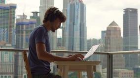 Νεαρός άνδρας freelancer workes στο lap-top του σε ένα μπαλκόνι με ένα υπόβαθρο ενός κεντρικού συνόλου πόλεων των ουρανοξυστών απ απόθεμα βίντεο