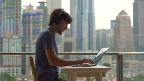 Νεαρός άνδρας freelancer workes στο lap-top του σε ένα μπαλκόνι με ένα υπόβαθρο ενός κεντρικού συνόλου πόλεων των ουρανοξυστών αν φιλμ μικρού μήκους
