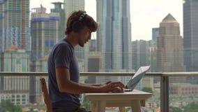Νεαρός άνδρας freelancer workes στο lap-top του σε ένα μπαλκόνι με ένα υπόβαθρο ενός κεντρικού συνόλου πόλεων των ουρανοξυστών αν απόθεμα βίντεο