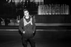 Νεαρός άνδρας έξω από το κάθισμα δίπλα στη μεγάλη πηγή Στοκ Εικόνες