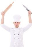 Νεαρός άνδρας αρχιμαγείρων καρφίτσα κυλίνδρων εκμετάλλευσης και μαχαίρι που απομονώνεται στην ομοιόμορφη Στοκ φωτογραφία με δικαίωμα ελεύθερης χρήσης