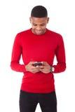Νεαρός άνδρας αφροαμερικάνων που στέλνει ένα μήνυμα κειμένου στο smartph της Στοκ εικόνα με δικαίωμα ελεύθερης χρήσης