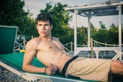 Νεαρός άνδρας γυμνοστήθων που κάνει ηλιοθεραπεία στην έδρα σαλονιών επάνω Στοκ Εικόνες