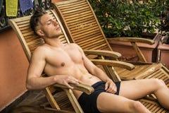 Νεαρός άνδρας γυμνοστήθων που κάνει ηλιοθεραπεία στην έδρα σαλονιών Στοκ Φωτογραφίες