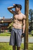 Νεαρός άνδρας γυμνοστήθων που στηρίζεται μετά από το workout υπαίθριο Στοκ Φωτογραφίες