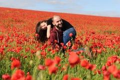 Νεαρός άνδρας και γυναίκα που έχουν την ημερομηνία στον τομέα των παπαρουνών στοκ εικόνα με δικαίωμα ελεύθερης χρήσης