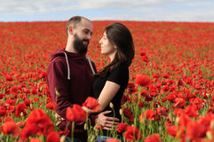 Νεαρός άνδρας και γυναίκα που έχουν την ημερομηνία στον τομέα των παπαρουνών Στοκ φωτογραφίες με δικαίωμα ελεύθερης χρήσης