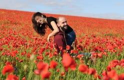 Νεαρός άνδρας και γυναίκα που έχουν την ημερομηνία στον τομέα των παπαρουνών στοκ φωτογραφία