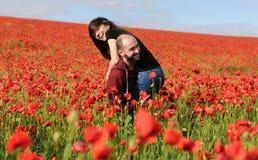 Νεαρός άνδρας και γυναίκα που έχουν την ημερομηνία στον τομέα των παπαρουνών στοκ εικόνα