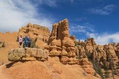 Νεαρός άνδρας και 2 νέες γυναίκες ερευνούν τους ζωηρόχρωμους σχηματισμούς βράχου του κόκκινου φαραγγιού Γιούτα Στοκ Εικόνες