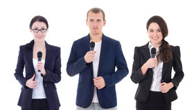Νεαρός άνδρας και δύο δημοσιογράφοι γυναικών με τα μικρόφωνα που απομονώνονται στο W Στοκ Εικόνα