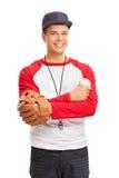 Νεαρός άνδρας με ένα γάντι μπέιζ-μπώλ που κρατά ένα μπέιζ-μπώλ Στοκ Φωτογραφία