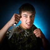 0 νεαρός άνδρας με ένα μαχαίρι Στοκ Εικόνες