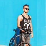 Νεαρός άνδρας με ένα ποδήλατο κοντά σε έναν φωτεινό μπλε τοίχο Μπλούζα με το τ Στοκ Εικόνες