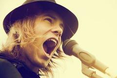 Νεαρός άνδρας με μακρυμάλλη και καπέλο που φωνάζει στο μικρόφωνο Τρύγος, μουσική Στοκ φωτογραφία με δικαίωμα ελεύθερης χρήσης
