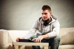 Νεαρός άνδρας με τα ακουστικά ταμπλετών που κάθεται στον καναπέ Στοκ εικόνες με δικαίωμα ελεύθερης χρήσης