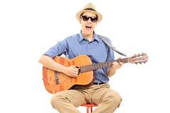Νεαρός άνδρας με τα γυαλιά ηλίου και παιχνίδι καπέλων στην ακουστική κιθάρα Στοκ Φωτογραφίες