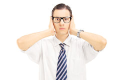 Νεαρός άνδρας με τα γυαλιά που καλύπτουν τα αυτιά του με τα χέρια Στοκ φωτογραφία με δικαίωμα ελεύθερης χρήσης