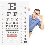 Νεαρός άνδρας με τα γυαλιά που κρυφοκοιτάζει πίσω από τη δοκιμή όρασης Στοκ Φωτογραφία