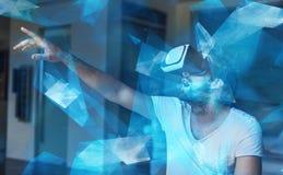 Νεαρός άνδρας με τα γυαλιά VR που παίζει την εικονική πραγματικότητα με την μπλε πυράκτωση Στοκ φωτογραφία με δικαίωμα ελεύθερης χρήσης