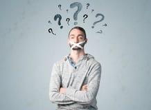 Νεαρός άνδρας με τα κολλημένα σύμβολα στομάτων και ερωτηματικών στοκ εικόνες