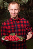 Νεαρός άνδρας με τα φρούτα του κραταίγου Στοκ Εικόνες