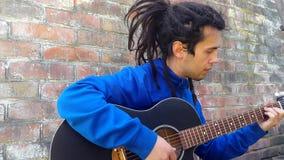 Νεαρός άνδρας με τα dreadlocks που παίζουν σε μια ακουστική κιθάρα σε ένα υπόβαθρο τουβλότοιχος φιλμ μικρού μήκους