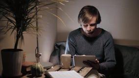 Νεαρός άνδρας με την αφή PC ταμπλετών σε έναν καφέ που έχει κάποιο φλυτζάνι καφέ Στοκ φωτογραφία με δικαίωμα ελεύθερης χρήσης