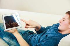 Νεαρός άνδρας με την ψηφιακή ταμπλέτα που βάζει στον καναπέ Στοκ Εικόνες