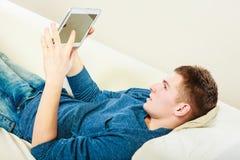 Νεαρός άνδρας με την ψηφιακή ταμπλέτα που βάζει στον καναπέ Στοκ Εικόνα