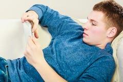 Νεαρός άνδρας με την ψηφιακή ταμπλέτα που βάζει στον καναπέ Στοκ φωτογραφία με δικαίωμα ελεύθερης χρήσης