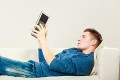 Νεαρός άνδρας με την ψηφιακή ταμπλέτα που βάζει στον καναπέ Στοκ φωτογραφίες με δικαίωμα ελεύθερης χρήσης