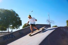 Νεαρός άνδρας με τη γενειάδα και δερματοστιξίες που κάνουν πατινάζ στο longboard Στοκ Φωτογραφία