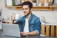 Νεαρός άνδρας με τη γενειάδα που λειτουργεί στο lap-top Στοκ εικόνες με δικαίωμα ελεύθερης χρήσης