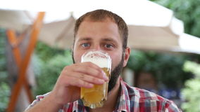 Νεαρός άνδρας με τη γενειάδα που πίνει τη frothy μπύρα απόθεμα βίντεο