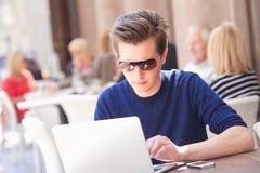 Νεαρός άνδρας με τη συνεδρίαση lap-top στο εξωτερικό καφέ Στοκ Εικόνες