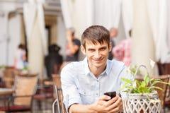 Νεαρός άνδρας με τη συνεδρίαση smartphone στον καφέ Στοκ φωτογραφίες με δικαίωμα ελεύθερης χρήσης