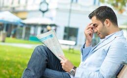 Νεαρός άνδρας με τις εφημερίδες μιας headashe εκμετάλλευσης Στοκ φωτογραφία με δικαίωμα ελεύθερης χρήσης