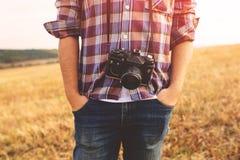 Νεαρός άνδρας με τον αναδρομικό φωτογραφιών τρόπο ζωής hipster καμερών υπαίθριο Στοκ φωτογραφία με δικαίωμα ελεύθερης χρήσης