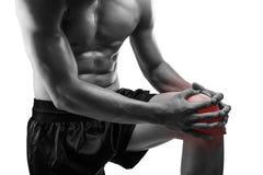 Νεαρός άνδρας με τον πόνο γονάτων, που απομονώνεται στο άσπρο υπόβαθρο, monochrom Στοκ Εικόνες