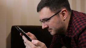 Νεαρός άνδρας με τον υπολογιστή ταμπλετών που βρίσκεται διαβασμένες στις καναπές αστείες ειδήσεις φιλμ μικρού μήκους